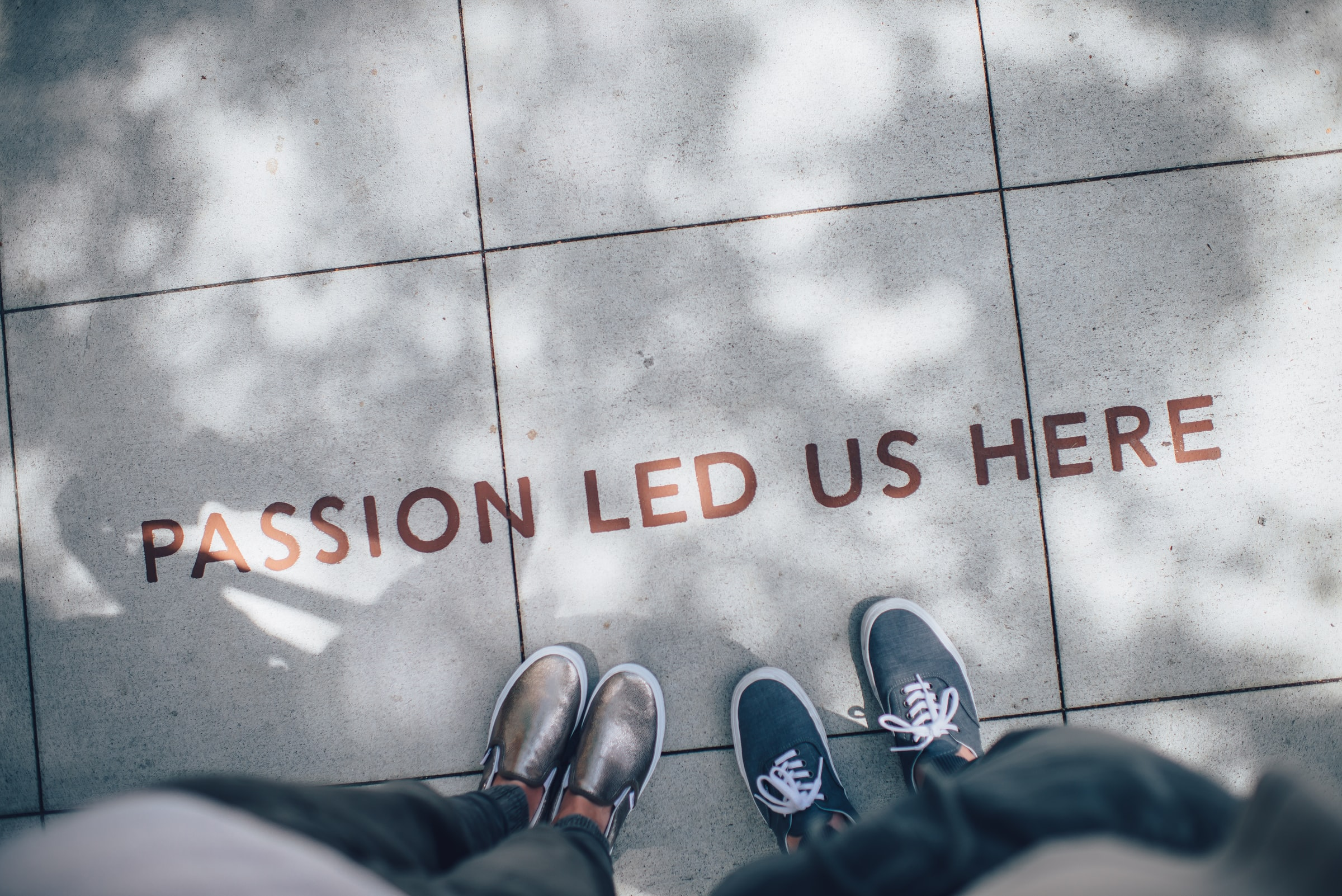 'Passion Led Us Here' written on pavement about two peoples feet.